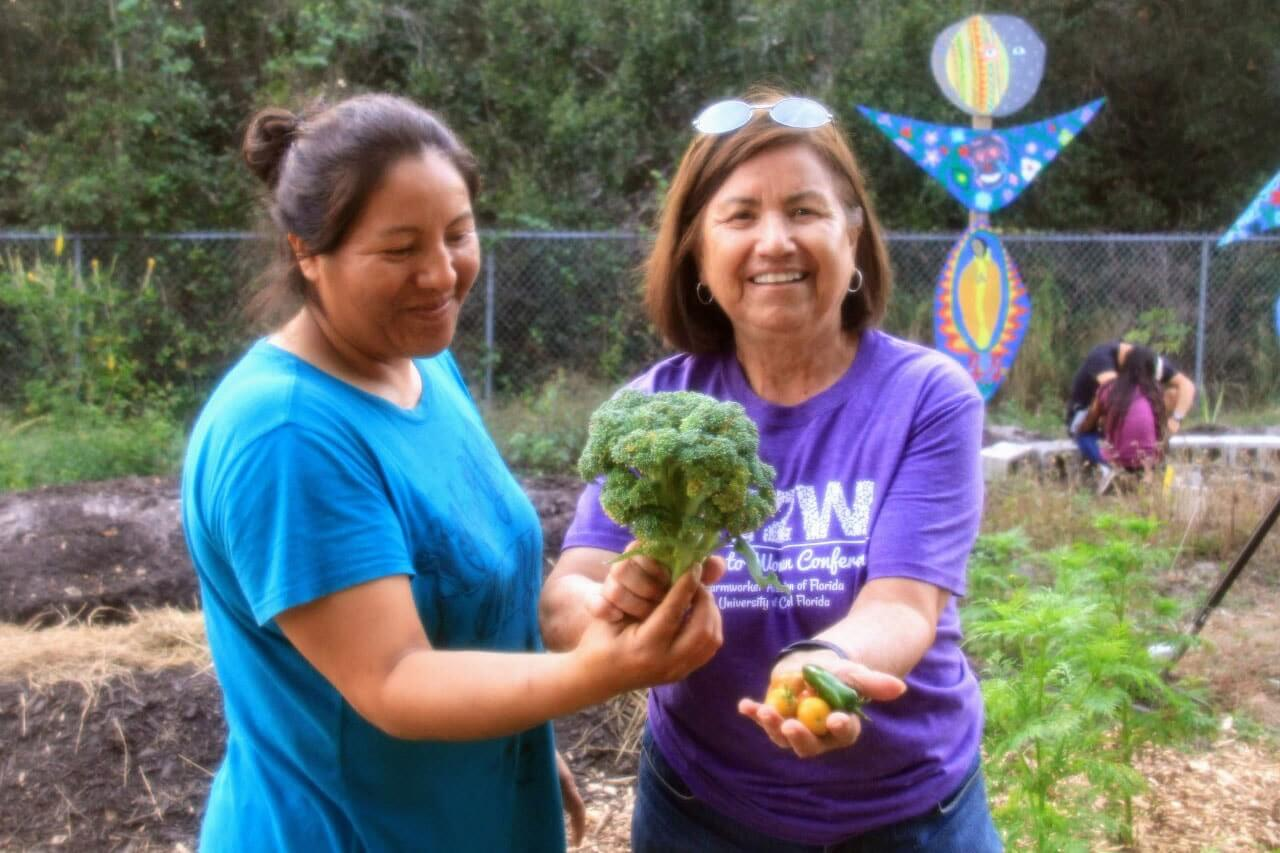 Two women holding up vegetables for camera